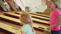 A little girl celebrates a victory playing skee ball Stock Footage