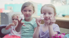 Little girls eating cotton candy at a fair - stock footage