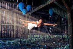 Young woman blue balloons levitation Stock Photos