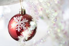 Red bauble hangning from white branch wrapped in tinsel Stock Photos
