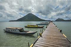 Jetty of Lonthor the volcano Gunung Api behind Banda Islands Moluccas Indonesia - stock photo