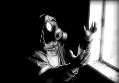 Person with gas mask looking into the bright light creative image worshiping - stock photo
