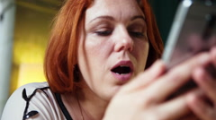 Closeup portrait anxious adult women looking at phone seeing bad news or photos Stock Footage