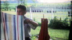 2592 - young boy hangs laundry on clothesline - vintage film home movie - stock footage