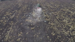 Slow motion, aerial view of tractor plowing a field with flock of cattle egrets Stock Footage