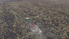 slow motion, aerial view of tractor plowing a field with flock of cattle egrets - stock footage