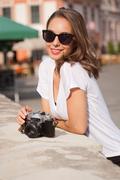 Brunette woman using analog camera. - stock photo