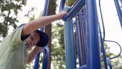 Cute Little Boy Climbs Ladder On Play Structure, He Turns And Smiles Stock Footage