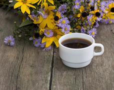 still life a cup of coffee and wild flowers on an old table - stock photo