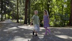Little Kids Walk Down Path In Park, Explore On Their Own (Slow Motion) Stock Footage