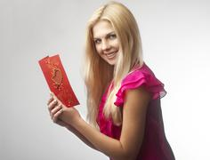 Portrait of happy young woman holding valentine card - stock photo