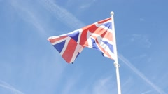 Slow motion waving United Kingdom famous striped flag in front of blue sky 19 Stock Footage