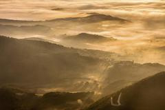 Stock Photo of Aerial view Mount Cucco Monte Cucco in the Apennines at sunset small village