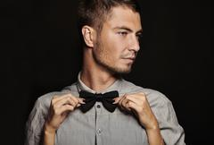 Fashion young man with women hands on black background.. Fashion young man wi - stock photo