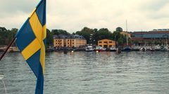 Swedish flag on Stockholm waterfront Stock Footage