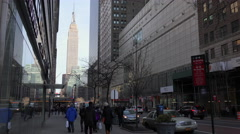 A Manhattan street scene with pedestrians and the Empire State Building in the Stock Footage