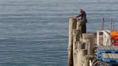 Fisherman in Halfmoon Bay on Stewart Island, New Zealand Stock Footage