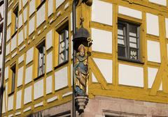 Stock Photo of Figure Saint Giles on an old half timbered house in the Weissgerbergasse
