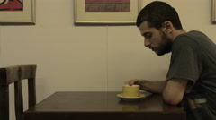 Young adult male drinks tea in a beautiful cafe Stock Footage