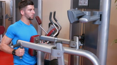Man using weights machine in gym Stock Footage