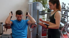 Couple using weights machine in gym Stock Footage