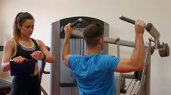 Fit man lifting weights with trainer Stock Footage
