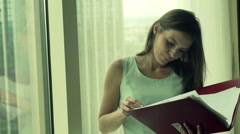 Pretty, young businesswoman reading and analyzing documents standing by window Stock Footage