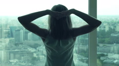 Young businesswoman stretching her arms and admire view from window Stock Footage