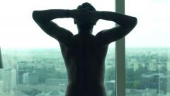 Young man stretching his arms, neck and admire view from window - stock footage