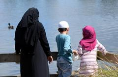 Immigrants muslim family feed ducks in a pond Stock Photos