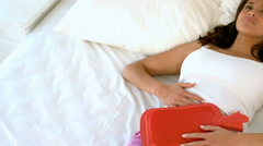 Woman lying in bed with cramps Stock Footage
