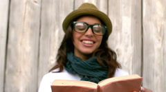 Hipster reading against wooden fence Stock Footage