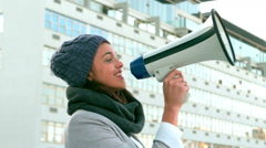 Hipster shouing through megaphone outside Stock Footage