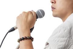 Stock Photo of Man and hand holding Microphone stand sing song isolated on white background,