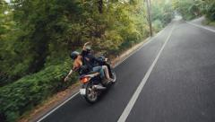 Young couple rides scooter on country road and girl spreads her arms Stock Footage