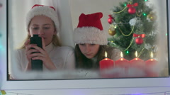 Little girls with gifted new smart phones at home near Christmas tree Stock Footage