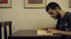 Young adult male reads a book and takes a sip from his tea - stock footage