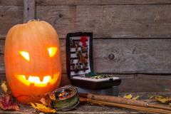Halloween pumpkin head with fly-fishing tackles Stock Photos