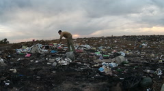 Man unemployed homeless dirty looking food waste in landfill dump  social video Stock Footage