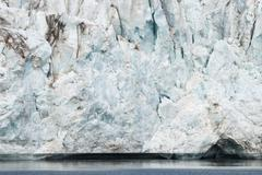 Close up of blue ice in the glacier by the sea, Svalbard - stock photo