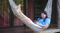 Asian woman relax on a hammock using smartphone - stock footage