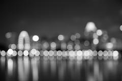 Singapore city night lights blurred bokeh black and white - stock photo