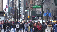 People walk on a street in Midtown Manhattan in the rain with traffic passing. - stock footage