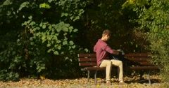 Man in Glasses is Sitting on Bench Closing His Backpack Freelance Copywriter Stock Footage