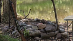 Shotgun stands at the extinct fire on the river bank.. Stock Footage