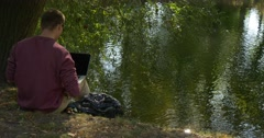 Man is Sitting at the River Bank Slope Working with Laptop Freelance Programmer Stock Footage