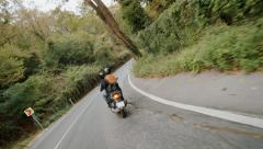 Slow motion shot of young couple on motorbike taking a steep turn Stock Footage