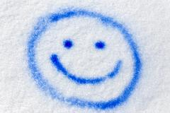 blue smiley sprayed in the snow - stock photo