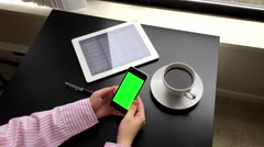Woman holding a green screen iphone with global exchange rate app on ipad Arkistovideo
