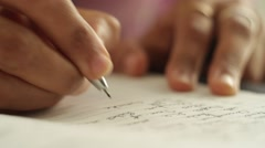 Close up of a man writing a proposal with a pen - stock footage